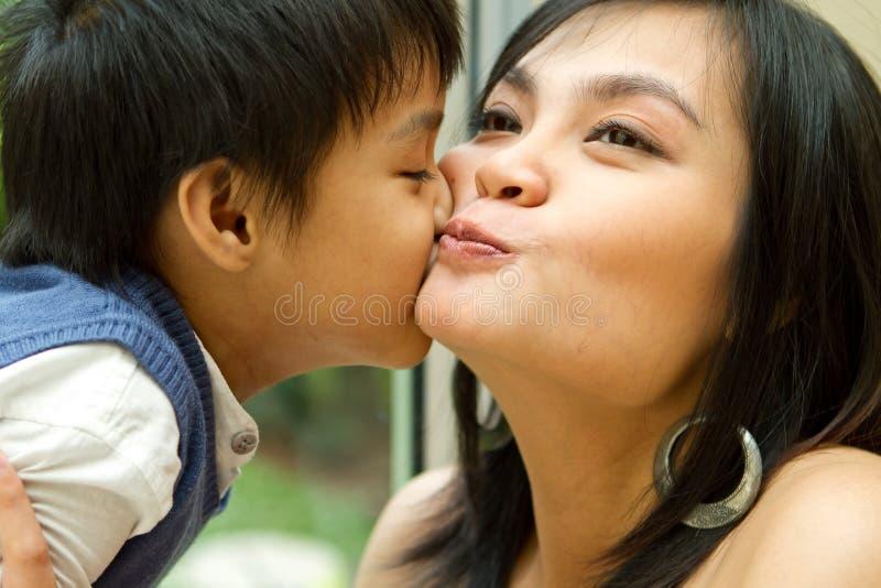 Het Aziatische jongen en moeder kussen stock afbeelding