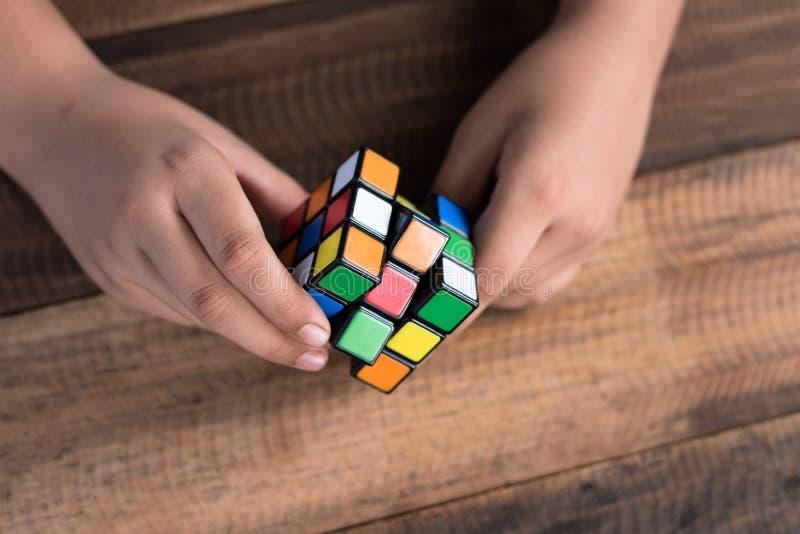 Het Aziatische jongen spelen met rubik` s kubus jongen die raadsel oplossen stock foto