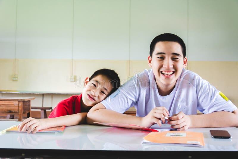 Het Aziatische Jongens glimlachen, die van studie genieten stock afbeelding