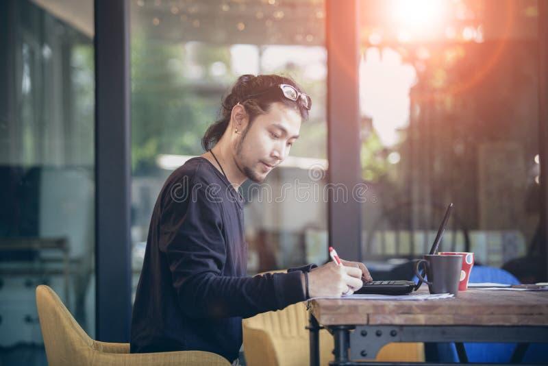 Het Aziatische jongere freelance werken in huisbureau stock afbeelding