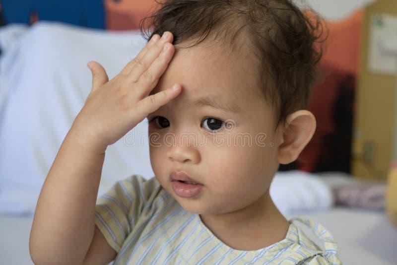 Het Aziatische kind houdt een hand voor een hoofd stock fotografie
