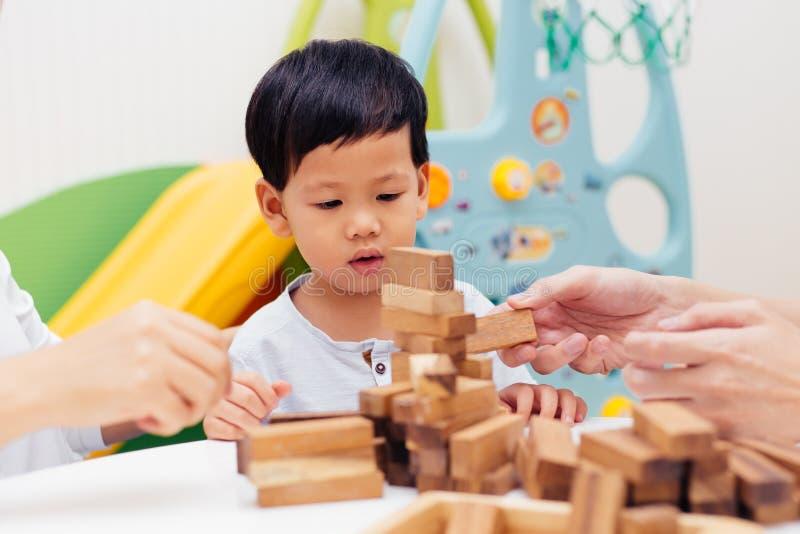Het Aziatische kind spelen met houten blokken in de ruimte thuis Een ki stock afbeeldingen