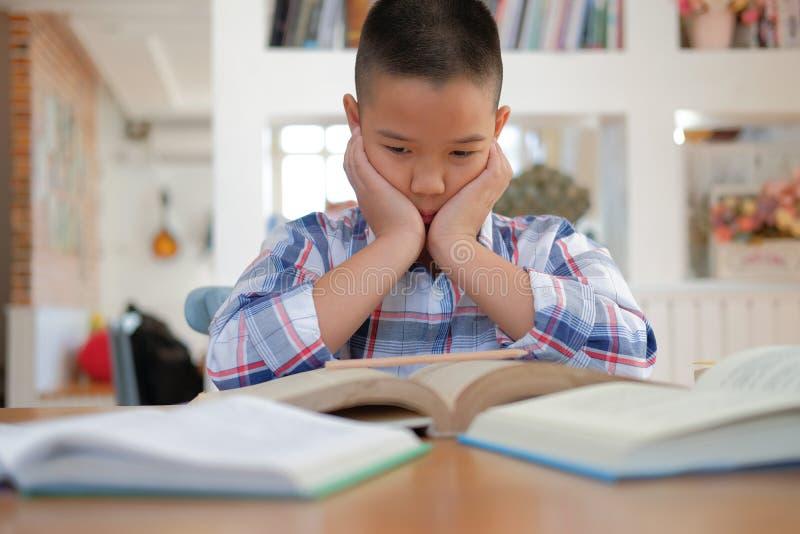 het Aziatische kind van de jong geitjejongen beklemtoonde vermoeid gefrustreerd bored van studyin stock afbeelding