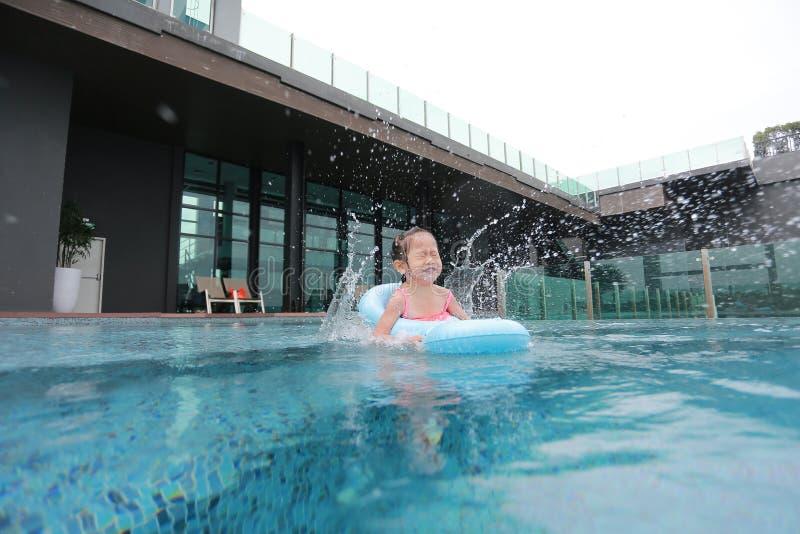Het Aziatische Kindmeisje heeft pret en het springen in de pool stock foto