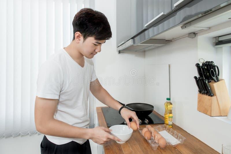 Het Aziatische Knappe mens koken in de keuken thuis stock afbeeldingen