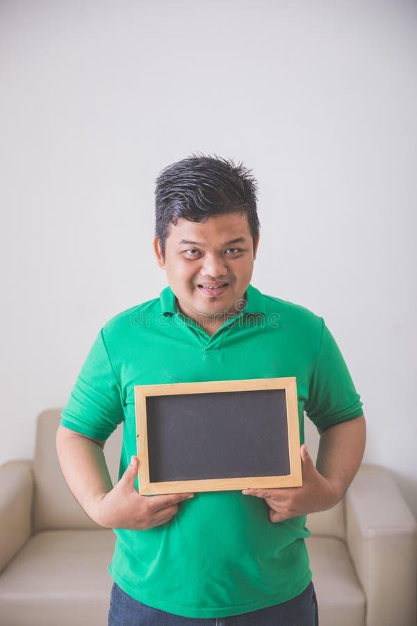 Het Aziatische mannelijke glimlachen aan het lege schoolbord van de cameraholding royalty-vrije stock afbeelding