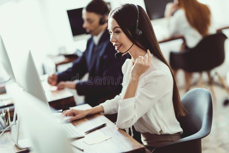 Het Aziatische meisje beantwoordt vragen van cliënten in het call centre royalty-vrije stock afbeelding