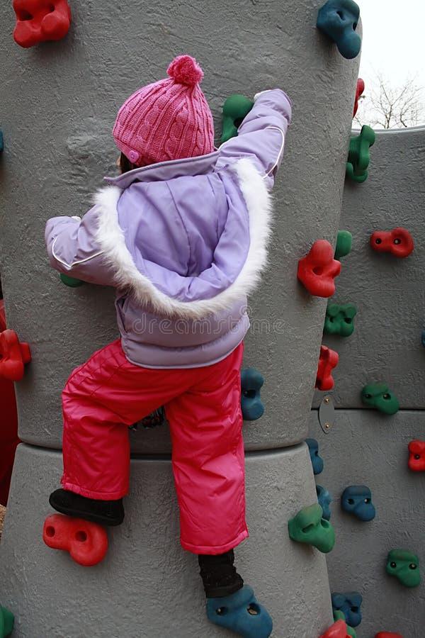 Het Aziatische meisje bundelde voor de winter beklimmend rotsmuur royalty-vrije stock foto's
