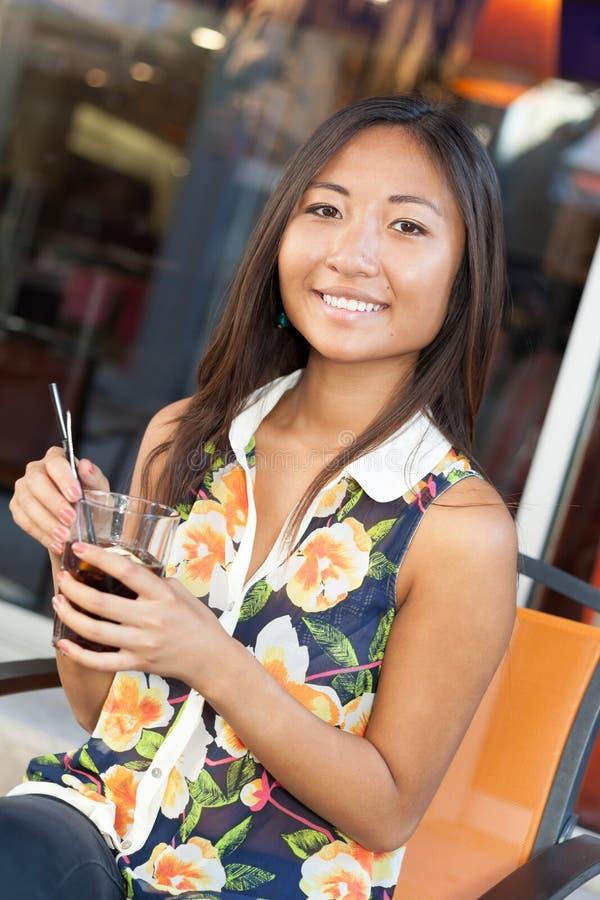 Het Aziatische meisje drinken op terras royalty-vrije stock foto