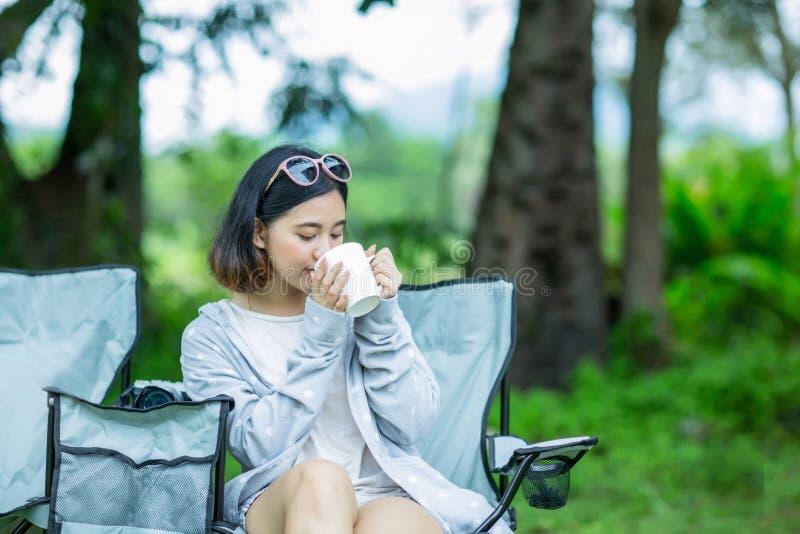 Het Aziatische meisje geniet van drinkend koffie in de tuin royalty-vrije stock afbeeldingen