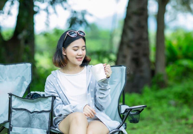 Het Aziatische meisje geniet van drinkend koffie in de tuin stock foto's