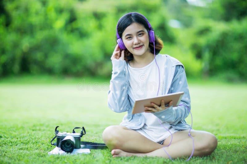 Het Aziatische meisje geniet van luister aan muziek in de tuin stock fotografie