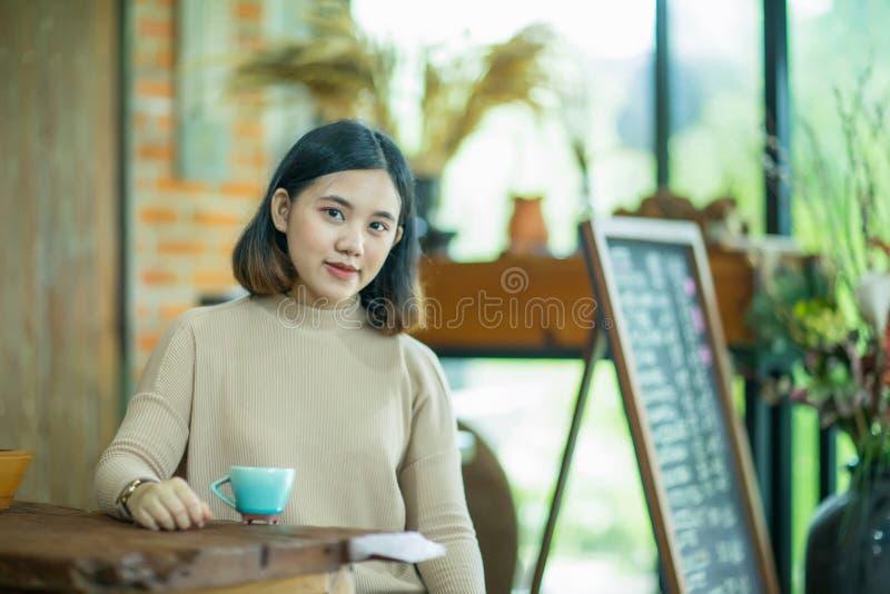 Het Aziatische meisje geniet van met koffie in de koffie royalty-vrije stock foto