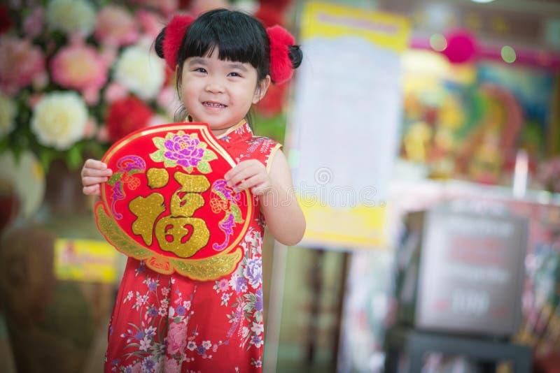 Het Aziatische meisje in het Chinese 'Gelukkige' couplet van de kledingsholding (Ruggegraat stock fotografie
