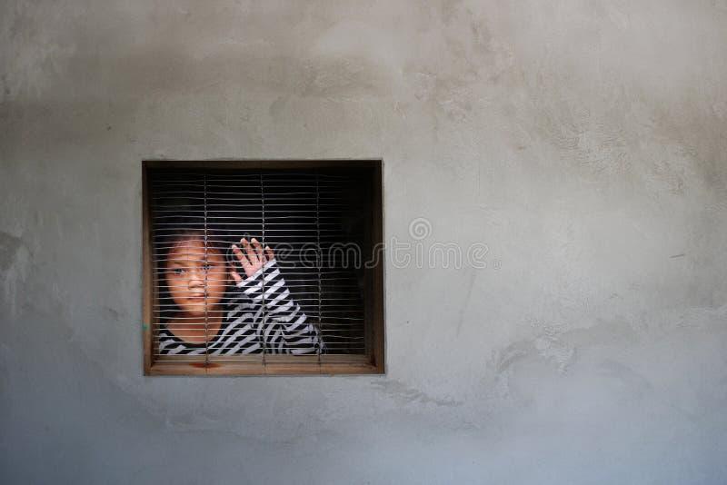 Het Aziatische meisje kijken werd uit het venster gevangengenomen in een huis, het Menselijke handel drijven stock foto