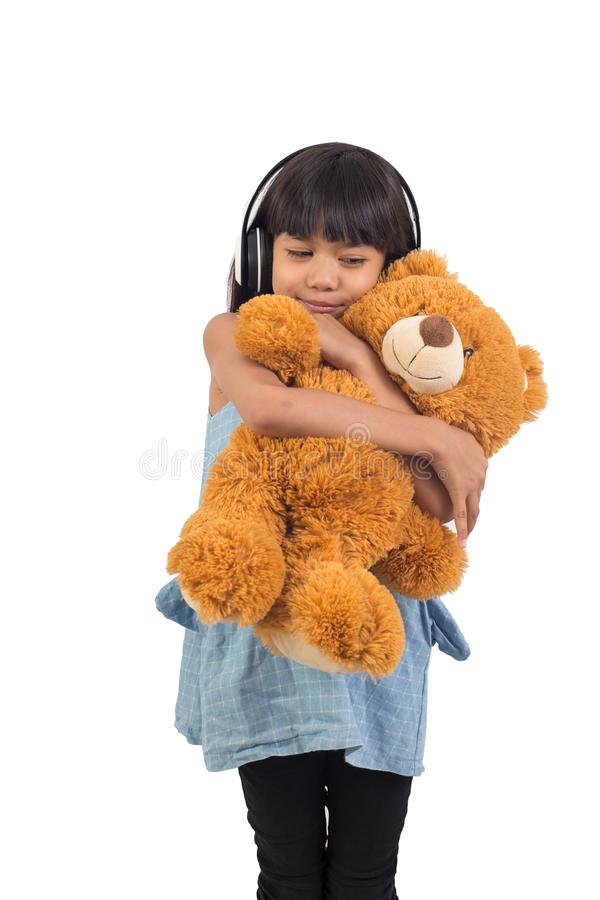 Het Aziatische meisje koestert een teddybeer op een wit stock afbeeldingen