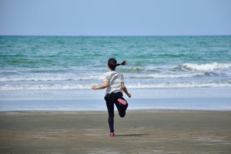 Het Aziatische meisje komt op het strand tegen het overzees stock afbeeldingen