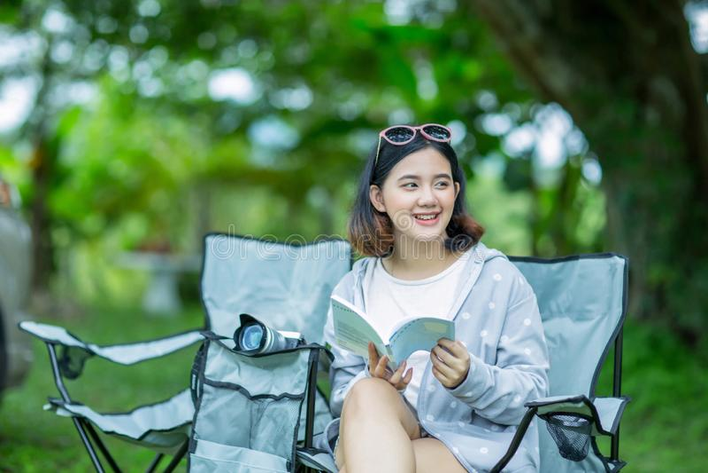Het Aziatische meisje ontspant met een boek in de tuin stock afbeeldingen