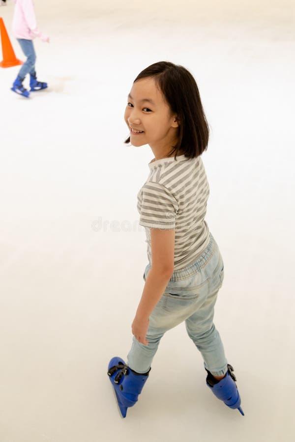 Het Aziatische meisje op de het schaatsen piste in blauwe schaatsen, glimlacht gelukkig het leuke ijs van het kindspel schaatsend royalty-vrije stock foto's
