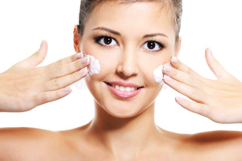 Het Aziatische meisje past kosmetische room op gezicht toe royalty-vrije stock afbeeldingen