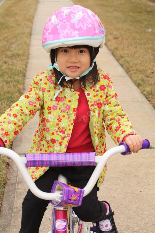 Het Aziatische meisje rideing op fiets met helm stock foto
