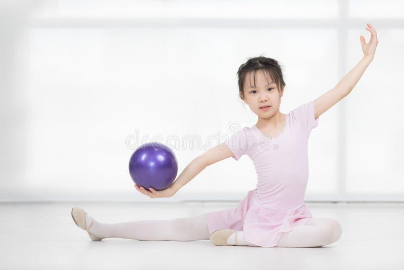 Het Aziatische meisje in roze kleding houdt bal stock afbeelding