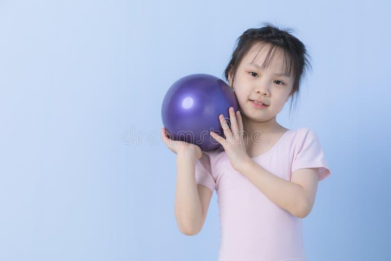 Het Aziatische meisje in roze kleding houdt bal stock foto