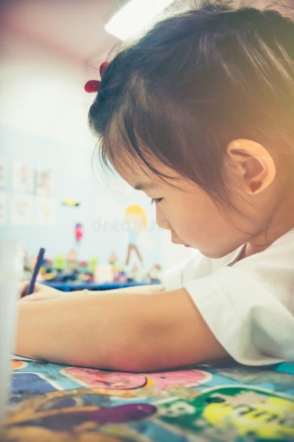 Het Aziatische meisje schilderen op kunstwerk met kleurpotlood Uitstekende toon royalty-vrije stock afbeelding