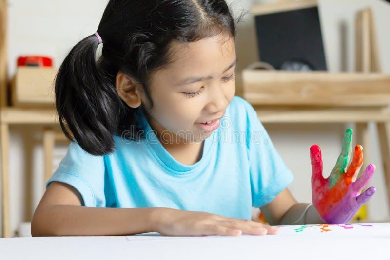 Het Aziatische meisje speelt kleur op de hand met geluk stock afbeeldingen