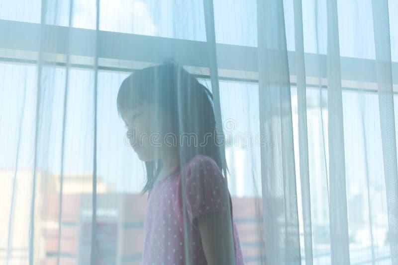 Het Aziatische meisje spelen achter het zuivere gordijn door groot venster met e stock afbeelding