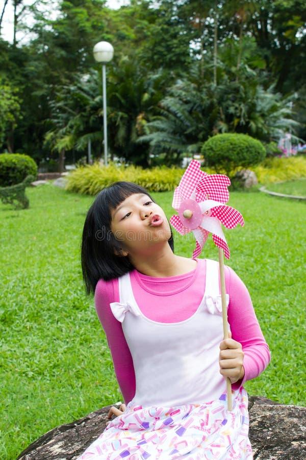 Het Aziatische meisje spelen met document windmolen stock fotografie