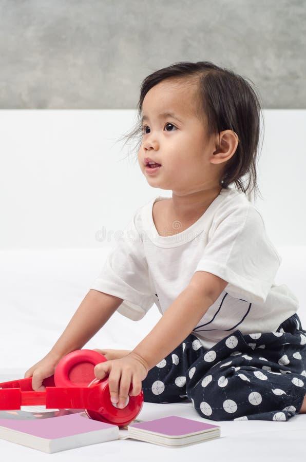 Het Aziatische meisje spelen met hoofdtelefoons en boek op het bed bij royalty-vrije stock afbeelding