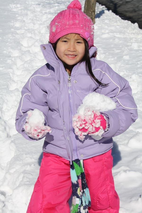 Het Aziatische meisje spelen in sneeuw met brokken royalty-vrije stock foto