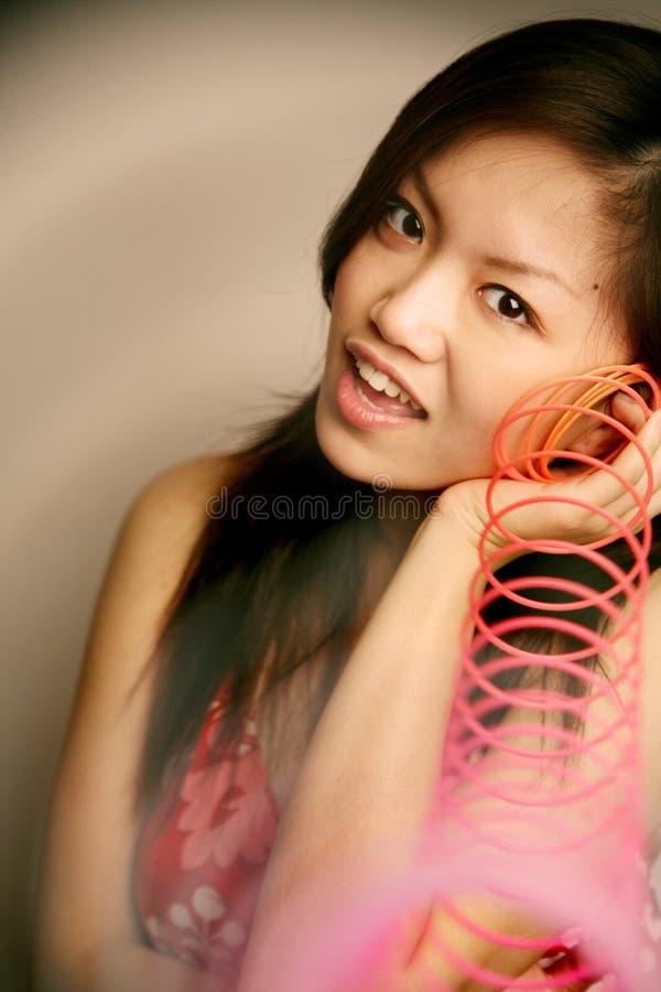 Het Aziatische meisje stiekem spelen stock foto