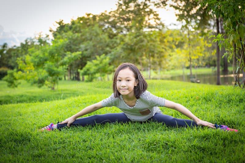 Het Aziatische meisje uitoefenen bij het openluchtpark op het gazon is een meditatiepraktijk, kindoefening in aard in de ochtend, royalty-vrije stock afbeeldingen