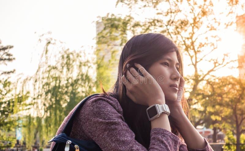 Het Aziatische meisje zit in het park royalty-vrije stock foto