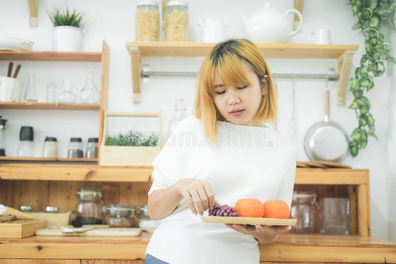 Het Aziatische mooie fruit en de groente van de vrouwenholding in de keuken bij haar huis stock foto's