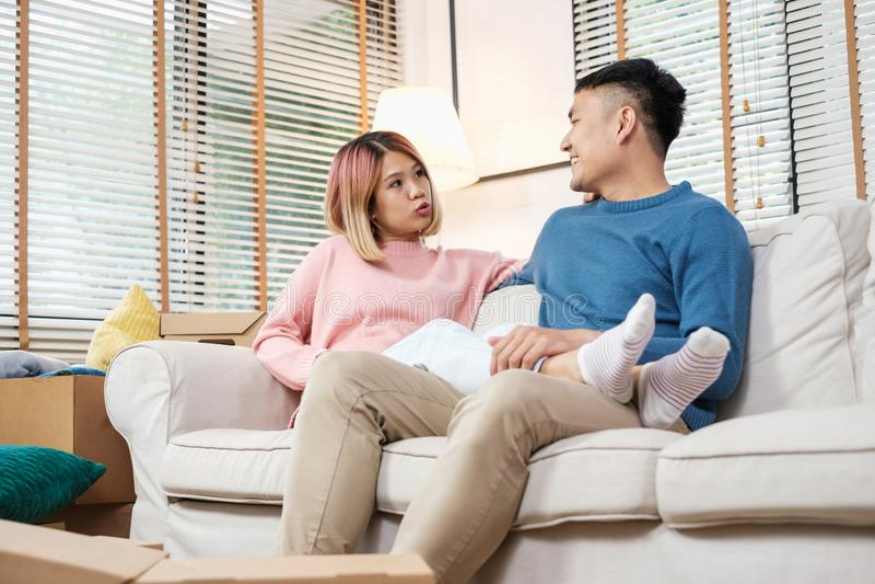 Het Aziatische paar die huis van plan zijn te verfraaien na zich het bewegen aan nieuw huis, die op bank zitten met ontspant emot royalty-vrije stock foto's