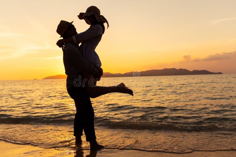 Het Aziatische paar die hun gevoel uitdrukken terwijl status bij strand, Jonge paren koestert bij het overzees bij zonsondergang royalty-vrije stock afbeeldingen