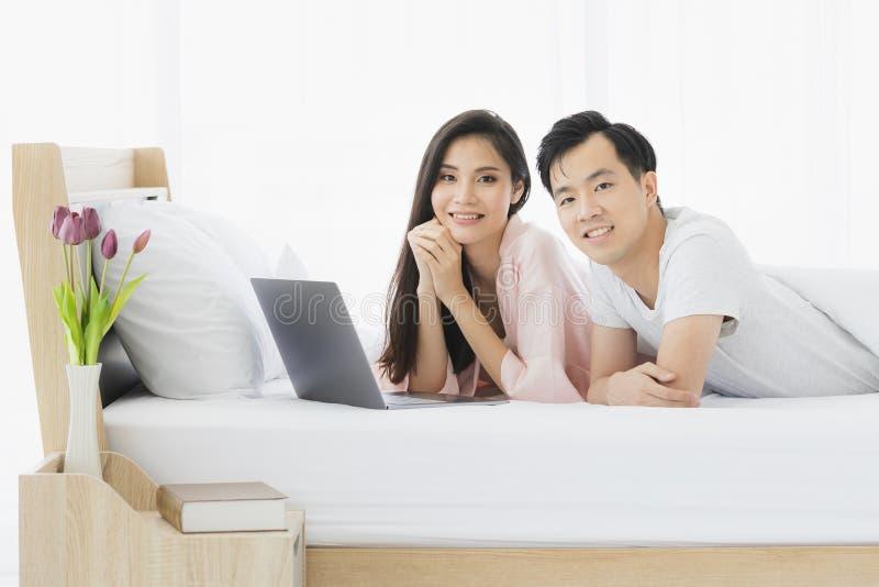 Het Aziatische paar ligt naar voren gebogen op bed in slaapkamer stock foto