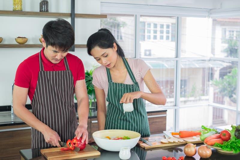 Het Aziatische paar in schort, maakt samen salades De mens treft voorbereidingen om groenten met messen te snijden De slasaus van stock afbeelding
