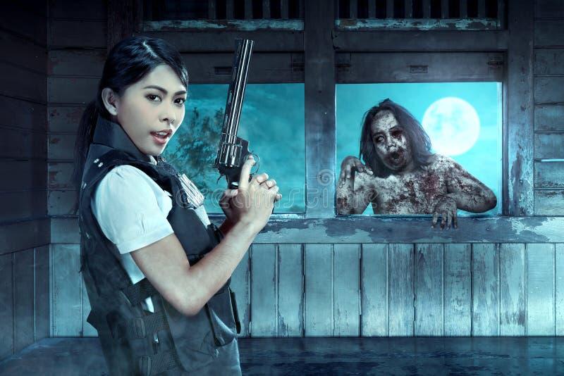 Het Aziatische politieagente met het kanon op zijn hand ziet de zombieën op de oude wagen onder ogen stock afbeelding