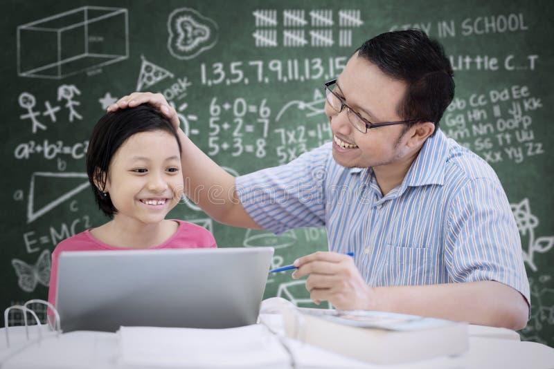 Het Aziatische schoolmeisje prijste door haar leraar royalty-vrije stock foto's
