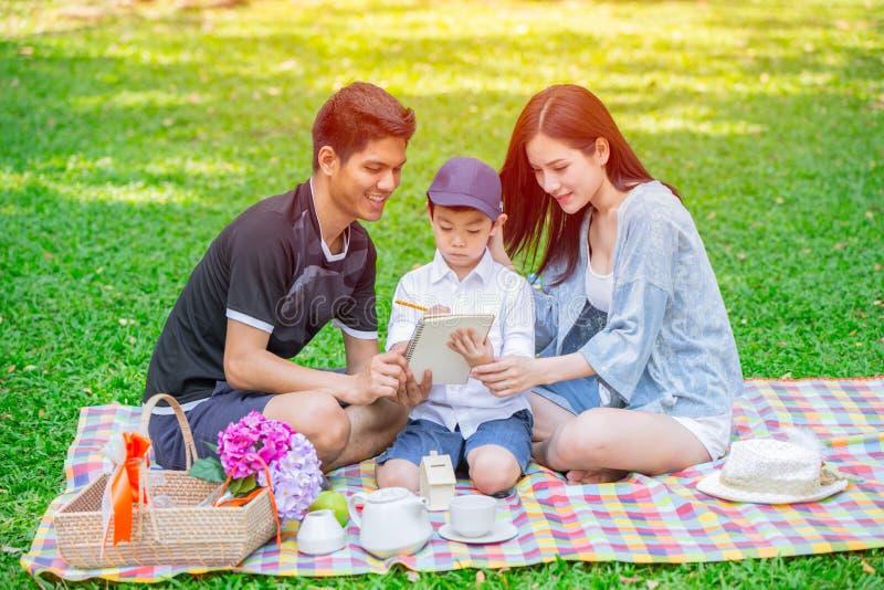 Het Aziatische teching onderwijs van de tienerfamilie aan picknick van de jong geitje de gelukkige vakantie stock foto