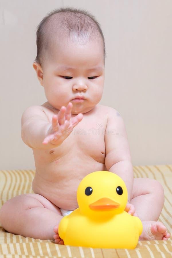 Het Aziatische Thaise babymeisje spelen met gele eend royalty-vrije stock foto