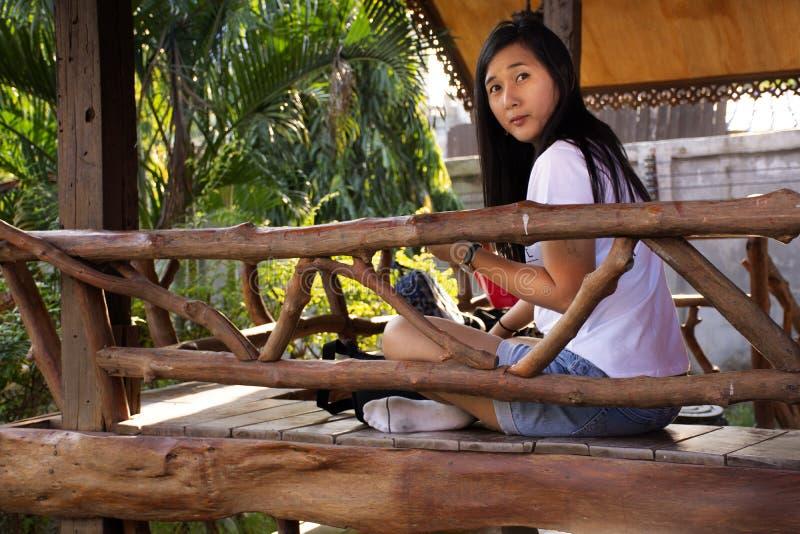 Het Aziatische Thaise bezoek en de zitting van de vrouwenreis op terras van houten hut van toevlucht en homestay voor het stellen royalty-vrije stock afbeelding