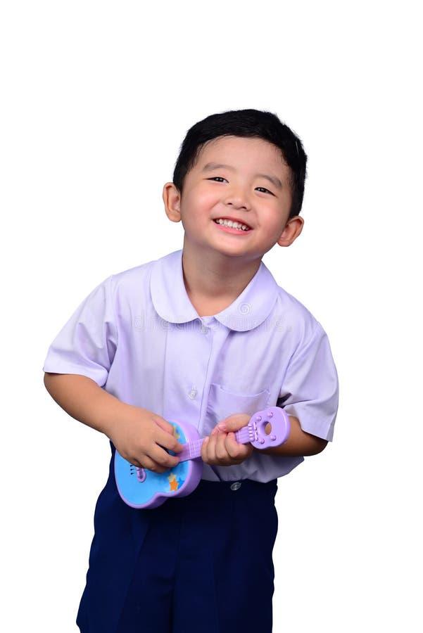 Het Aziatische Thaise jonge geitje van de kleuterschoolstudent in school eenvormige die het spelen stuk speelgoed gitaar op witte stock afbeelding