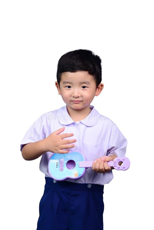 Het Aziatische Thaise jonge geitje van de kleuterschoolstudent in school eenvormige die het spelen stuk speelgoed gitaar op witte royalty-vrije stock afbeelding