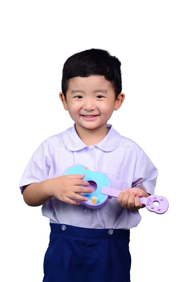 Het Aziatische Thaise jonge geitje van de kleuterschoolstudent in school het eenvormige spelen aan stock foto