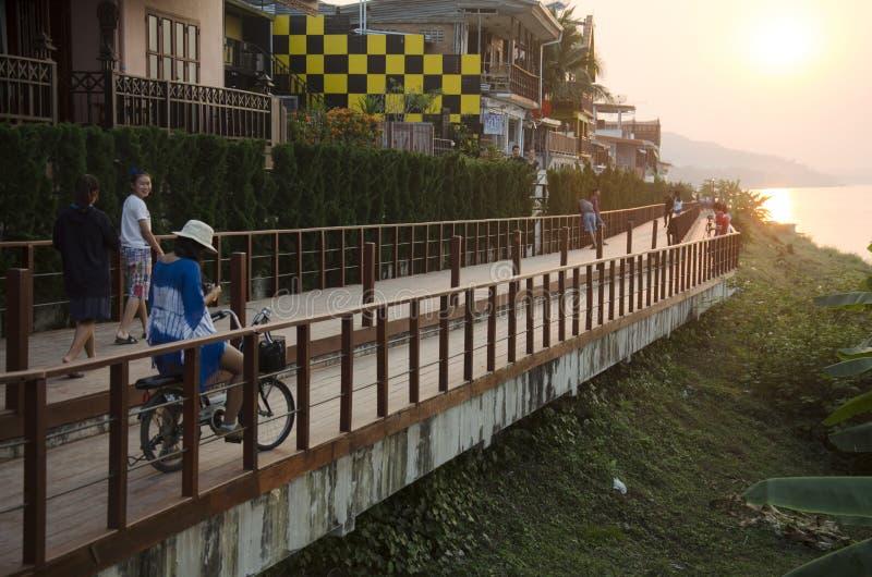 Het Aziatische Thaise vrouw stellen met fiets en reizigersmensen die ontspant bij rivieroevermekong rivier in Chiang Khan bij zon royalty-vrije stock foto